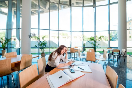 girl sit: Girl studying in the University canteen. general plan Stock Photo
