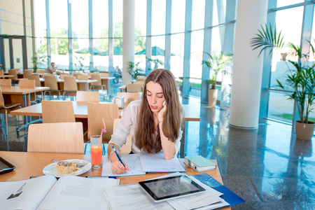 general knowledge: Girl studying in the University canteen with Fresh and cake Stock Photo