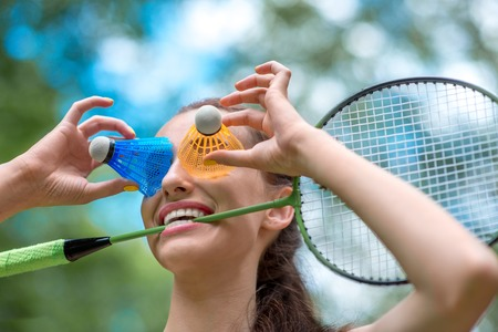 laughable: Sport woman with badminton racket and shuttlecock near her eyes in the park Stock Photo
