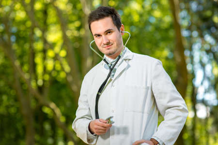 garden staff: Young doctor portrait with stethoscope on the green park background Stock Photo