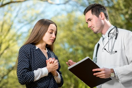 bad news: Doctor with bad news, talking to the patient in the park