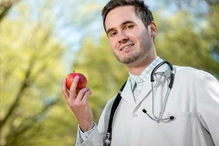 garden staff: Smiling doctor keeping an apple in hand in the park Stock Photo