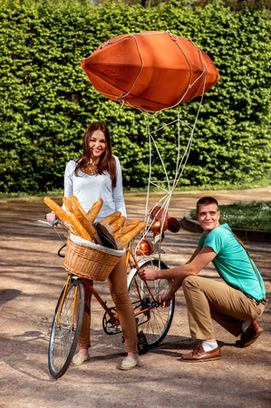 Young and joyful couple having fun in the park with bicycle and airship on it photo