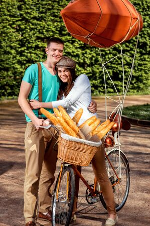 Young and joyful couple hugging in the park with bicycle and airship on it photo