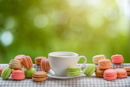Colorful macaroons with cup of coffee on the napkin on blurred green background 스톡 콘텐츠
