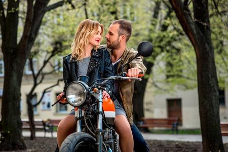 casco moto: Pareja sentada en la motocicleta en el parque de la ciudad