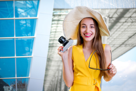 yellow dress: Young traveling woman with photo camera and dressed in yellow dress standing in front of the airport or high-tech background and looking toward