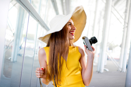 yellow dress: Young traveling woman with photo camera and panama dressed in yellow dress standing in front of the airport or high-tech background and looking toward Stock Photo