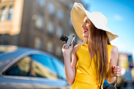 yellow dress: Young traveling woman with photo camera and panama, dressed in yellow dress walking on city background Stock Photo