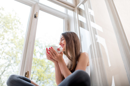 Young and cute lady sitting on the windowsill and looking out the window with cup of coffee in the morning