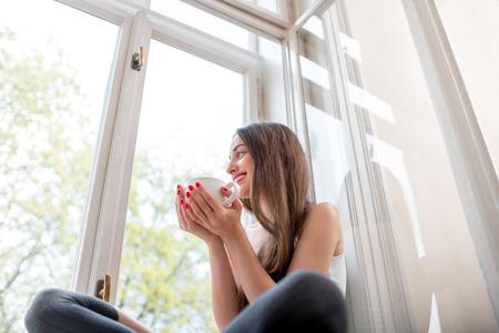 Jeune et mignon dame assise sur le rebord de la fenêtre et de regarder par la fenêtre avec tasse de café le matin