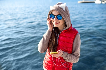 Young woman dressed in sportswear talking phone on the promenade near the water photo