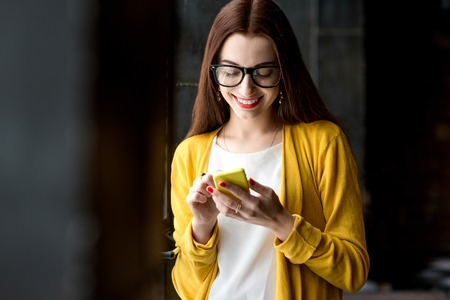 Young smiling woman dressed in yellow using phone near the window in the dark interior