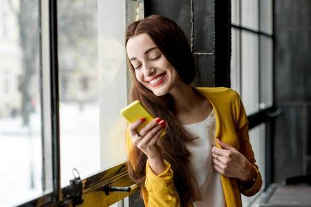 黄色、暗い室内に窓の近くに携帯電話を使用してに身を包んだ若い笑顔の女性
