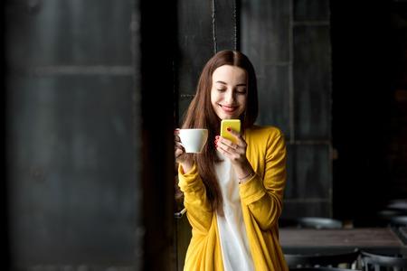 若いと黄色のセーターを使用してのきれいな女性の電話暗いカフェ インテリアで一杯のコーヒーを保持しています。