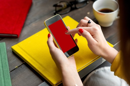 coffee table book: Woman using smart phone on the table with colorful books. Phone with empty screen for your application