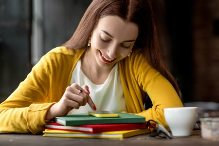 Young and smiling woman using smart phone on the colorful books in the dark interior background Фото со стока