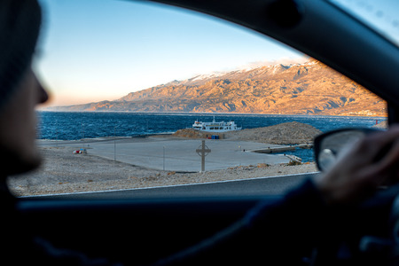 Croatian coasts with ferry floating on the sunset. View from the car with man driving