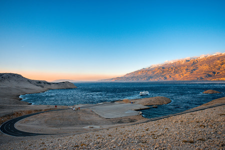 Croatian coasts with ferry floating on the sunset. Panorama view from the Pag island
