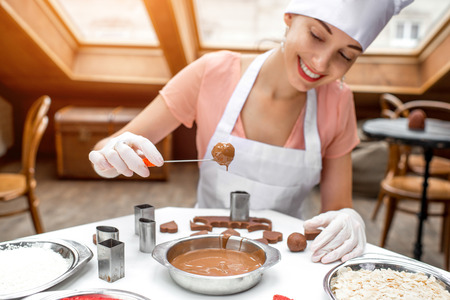 pinafore: Young smiling woman chef dressed in white pinafore making handmade chocolate candy in the cafe