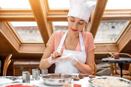 Young smiling woman chef dressed in white pinafore making handmade chocolate candy in the cafe photo