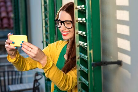 balcony window: Young woman in yellow sweater and glasses using mobile phone on the balcony with window shutters in old building. Stock Photo