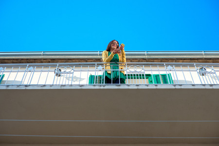 louver: Young woman in yellow sweater and glasses using mobile phone on the balcony with window shutters in old building. General plan.