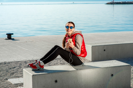 Sport woman dressed in warm clothes resting with phone and headphones after the excercise on the promenade in Spring. General plan with ship on background