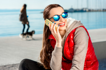 Sport woman dressed in warm clothes resting with phone and headphones after the exercise on the promenade in Spring photo