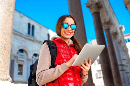 carryall: Young woman in warm sportswear with digital tablet traveling in the old city center. Traveling application concept Stock Photo