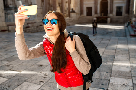 Young woman dressed in sportswear with smart phone traveling in the old city center photo