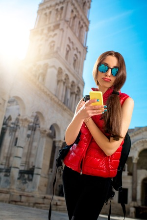 carryall: Young woman dressed in sportswear with smart phone traveling in the old city center