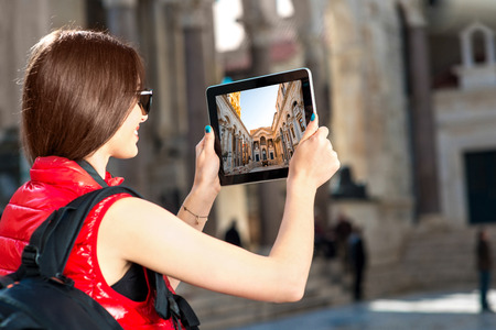 carryall: Young woman traveler photographing with tablet in the old city center Stock Photo