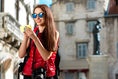 carryall: Young woman in red clothes with smart phone traveling in the old city center. Traveling application concept