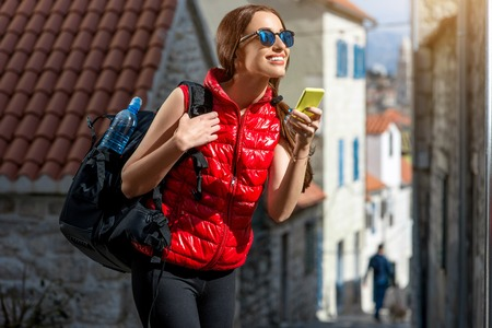 old cell phone: Young woman in red sportswear looking where to go with smart phone traveling in the old city center. Traveling application concept