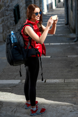 Young woman traveler in red sportswear photographing with smart phone old city street. photo