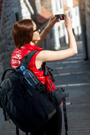 Young woman traveler in red sportswear taking selfie photo with smart phone in old city street in the morning. photo