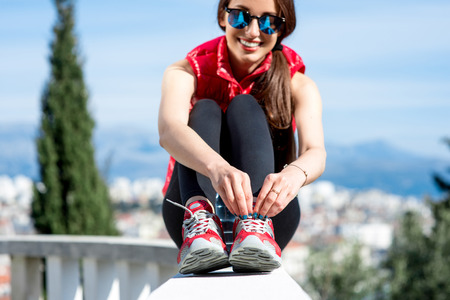 lacing sneakers: Young sporty woman in red clothes lacing the sneakers on the park alley with city view