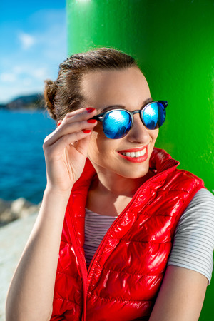 Sport woman puitting on sunglasses while sitting near the lighthouse on the beach photo