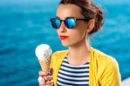 cono de helado: Mujer joven en el su�ter amarillo y gafas de sol celebraci�n helado en el fondo azul del agua