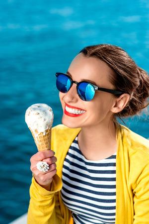 Junge Frau im gelben Pullover und eine Sonnenbrille essen Eis auf dem blauen Wasser Hintergrund Standard-Bild - 43029861