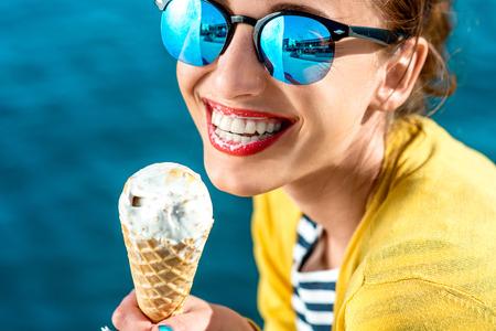 Mujer joven en suéter amarillo y gafas de sol que come el helado en el fondo azul del agua Foto de archivo