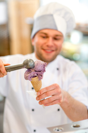 coif: Confectioner putting ice cream to the waffle cone in the pastry shop