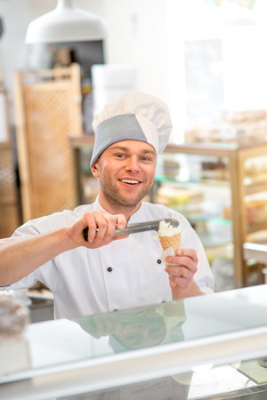 coif: Confectioner putting ice cream to the waffle cone in the store