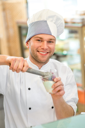 coif: Confectioner putting ice cream to the cup for takeaway in the store Stock Photo