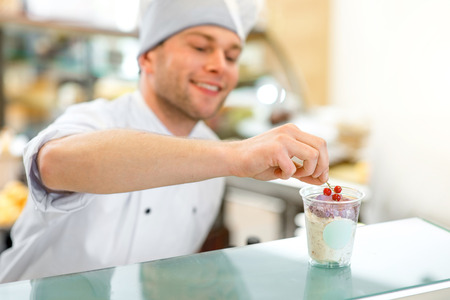 coif: Handsome confectioner decorating ice cream with berry in the store