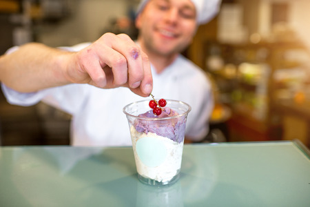 coif: Handsome confectioner decorating ice cream with berry in the pastry shop