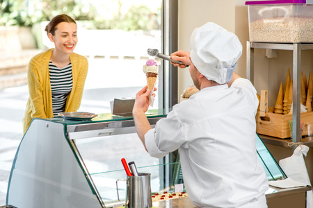 coif: Confectioner selling ice cream to young woman in the pastry shop