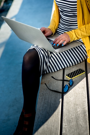 Young woman writer working with laptop on the wooden bench Stock Photo