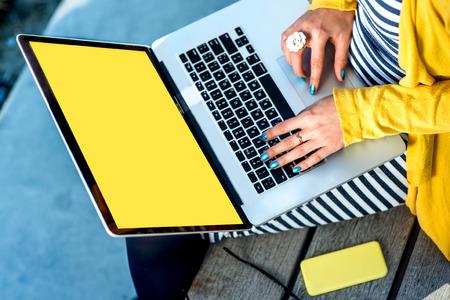 Mujer escribiendo en la computadora portátil con la pantalla amarilla vacía sentado en el banco